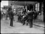 Marching band playing musical instruments outside store building