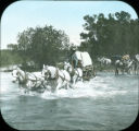 White Arms in wagon pulled by team of four horses crossing river in Wyoming 1