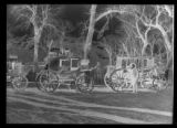 Negative of Buffalo Bill and two carriages
